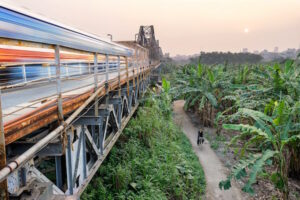 Take an Adventure on and below Long Bien Bridge Crossing the Red River in Hanoi